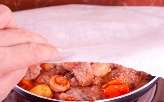 phủ giấy nướng vào chảo thịt