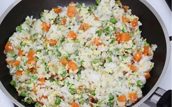 cho cơm vào chảo rau củ trứng
