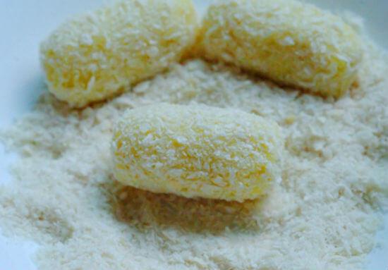 Lăn những miếng khoai tây bọc xúc xích qua bột chiên xù