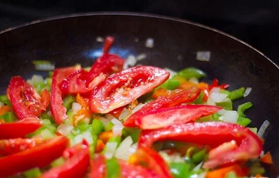 thêm cà chua vào chảo rau củ