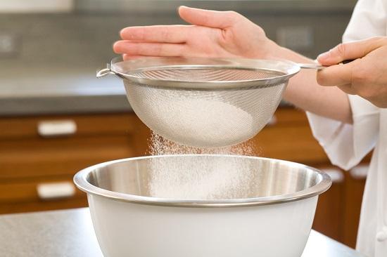 Rây bột vào hỗn hợp đường và nước cốt dừa - cách làm bánh bò nướng