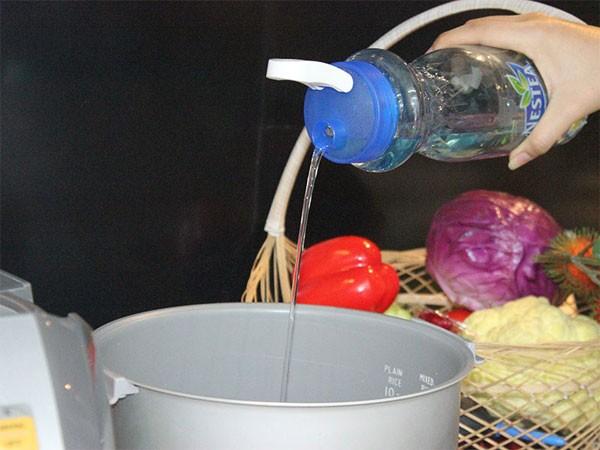 Làm bánh su kem - Đổ nước lọc vào nồi cơm điện và phủ 1 tấm giấy nướng bánh nên trên